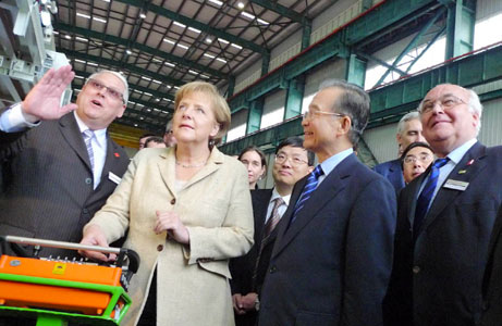 Chancellor Angela Merkel and Premier Wen Jiabao (centre left and right) hear of hi-tech TBM technology from Bernd Leuthner (left), Managing Director of Herrenknecht (Guangzhou) with Martin Herrenknecht (right), Chairman of the Board, looking on